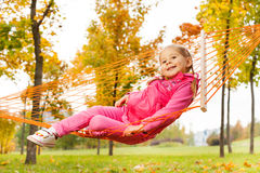 Blond girl laying on net of hammock in park Stock Photo