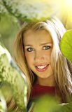 Blond girl in leafs. Beautiful smiling blond girl in leafs Royalty Free Stock Images