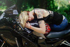 The blond girl lies on a motorcycle, smiles eyes, sensual and cheerful, hair closes her eyes royalty free stock image