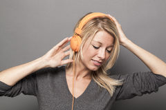 Blond girl listening to earphones with eyes closed Stock Photo