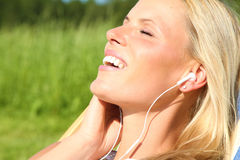Blond Girl listening to music. Beautiful blond girl is having fun and listening to music royalty free stock photo