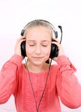 Blond girl listening to music with headset and is looking forward Stock Photo