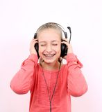 Blond girl listens to music with headphones and laughs Royalty Free Stock Image