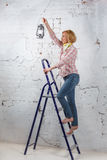 Blond girl with lit lantern standing on stepladder Stock Photography