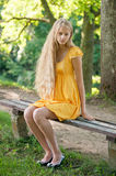 Blond Girl with long hair in yellow dress sitting on a bench Royalty Free Stock Images