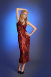 Blond girl in a long red  dress Stock Photos