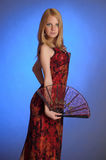 Blond girl in a long red  dress with a fan in hand Royalty Free Stock Photography
