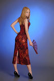 Blond girl in a long red  dress with a fan in hand Stock Photos