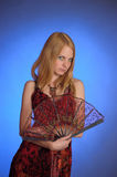 Blond girl in a long red  dress with a fan in hand Royalty Free Stock Image
