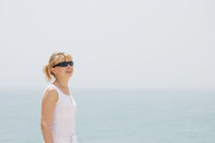 Blond girl looking at the blue ocean. Under the sky Royalty Free Stock Photography