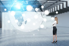 Blond girl looking at Earth hologram in office Royalty Free Stock Photography