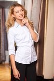 Blond girl looking at fabric in store. Royalty Free Stock Images