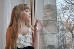 Blond  girl looking out the window Royalty Free Stock Photos