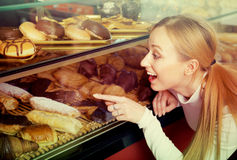 Blond girl looking into the pastry shop window and pointing Stock Image