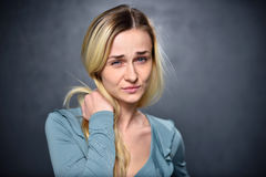 Blond girl looks suspiciously at the camera royalty free stock images