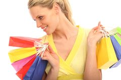 Blond girl with a lot of bags. Beautiful blond girl holding a lot of colored bags royalty free stock images