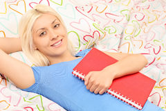 Blond girl lying in bed and holding a notebook Stock Image