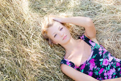 Blond girl is lying on haystack in summer sunny Royalty Free Stock Photos