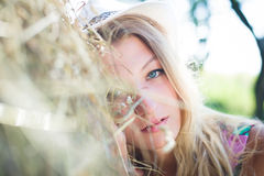 Blond girl is lying on haystack in summer sunny Stock Photos