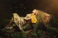 Blond girl in a magic forest. Blond girl dressed in dress walk in a magic forest Royalty Free Stock Photo