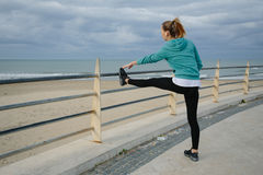 Blond girl makes exercises near sea Stock Image