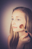 Blond girl, makeup brush trying to conceal, grain effect Royalty Free Stock Photography