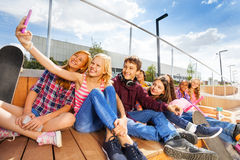 Blond girl making selfie of her and friends Royalty Free Stock Photography