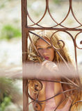 Blond girl in Mediterranean rusted gate at sea Royalty Free Stock Images