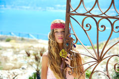 Blond girl in Mediterranean rusted gate at sea Stock Photos