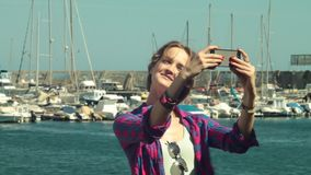 Blond girl model shooting selfie video photo a front of yacht club stock video