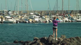 Blond girl model shooting video photo of yacht club stock video footage