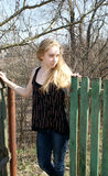 Blond girl near fence Royalty Free Stock Image