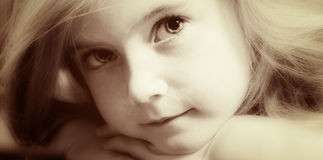 Blond girl in old sepia. Cute blond girl with strong eye-contact, lying on her hands Royalty Free Stock Photography