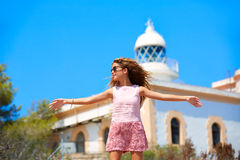 Blond girl open hands in Mediterranean Lighthouse. Feeling the wind in spain Royalty Free Stock Images