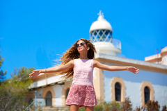 Blond girl open hands in Mediterranean Lighthouse. Feeling the wind in spain Royalty Free Stock Photos