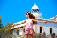 Blond girl open hands in Mediterranean Lighthouse. Feeling the wind in spain Royalty Free Stock Image