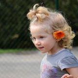 Blond girl with an orange flower in hair Stock Image