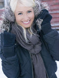 Blond girl outside red wooden shed. Blond girl outside red shed in wintertime stock photo