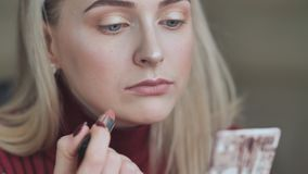 Blond girl paints her lips with lipstick with a dull red color. stock video footage
