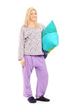 Blond girl in pajamas holding a pillow Royalty Free Stock Images
