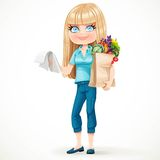 Blond girl with paper bag fresh fruits and vegetables and notepad Stock Image