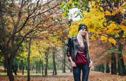 Blond girl in the park. Young girl with blond hair wearing a black cap with the inscription black moon, dressed in a leather jacket and Gina walks in the Royalty Free Stock Photo