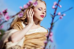 Blond girl in peach garden Stock Image