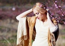 Blond girl in peach garden Stock Photos