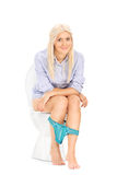 Blond girl peeing seated on a toilet Royalty Free Stock Images