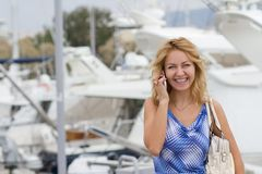 Blond girl with the phone on a pier Royalty Free Stock Image