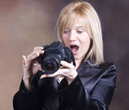 Blond girl with photo camera Royalty Free Stock Photos