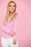 Blond girl in pink, standing full-length Stock Images