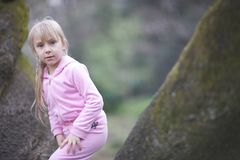 A blond girl in a pink suit walking. Portrait of a blond girl in a pink suit walking in a park Stock Image