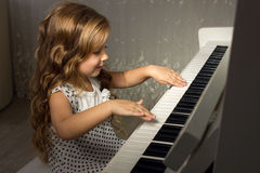 Blond girl playing a piano Royalty Free Stock Photography